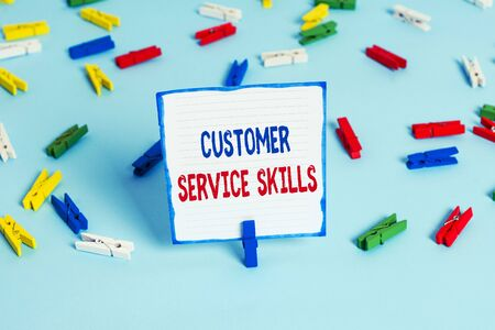 Foto de Conceptual hand writing showing Customer Service Skills. Concept meaning Aptitude to master to improve dealings with client Colored clothespin papers empty reminder blue floor officepin - Imagen libre de derechos