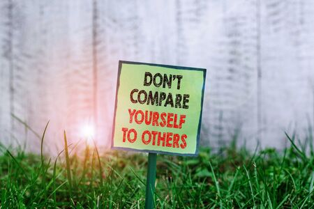 Photo for Conceptual hand writing showing Don T Compare Yourself To Others. Concept meaning Be your own version unique original Plain paper attached to stick and placed in the grassy land - Royalty Free Image