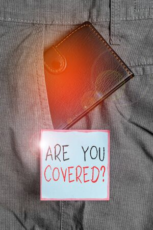 Foto de Writing note showing Are You Covered Question. Business concept for asking showing if they had insurance in work or life Small wallet inside trouser front pocket near notation paper - Imagen libre de derechos