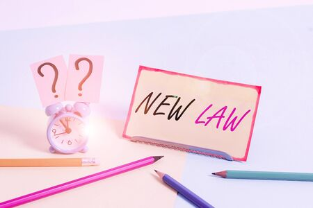 Handwriting text New Law. Conceptual photo system of rules that enforced through social or governmental Mini size alarm clock beside stationary placed tilted on pastel backdrop