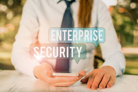 Word writing text Enterprise Security. Business photo showcasing decreasing the risk of unauthorized access to data Female business person sitting by table and holding mobile phone