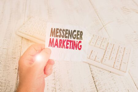 Writing note showing Messenger Marketing. Business concept for act of marketing to your customers using a messaging app Man holding colorful reminder square shaped paper wood floor