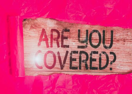 Foto de Conceptual hand writing showing Are You Covered Question. Concept meaning asking showing if they had insurance in work or life Cardboard which is torn placed above a wooden classic table - Imagen libre de derechos