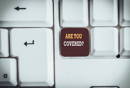 Foto de Text sign showing Are You Covered Question. Business photo text asking someone or patient if he have insurance White pc keyboard with empty note paper above white background key copy space - Imagen libre de derechos
