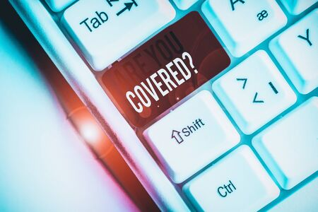 Foto de Conceptual hand writing showing Are You Covered Question. Concept meaning asking showing if they had insurance in work or life White pc keyboard with note paper above the white background - Imagen libre de derechos