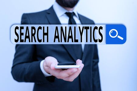 Foto de Writing note showing Search Analytics. Business concept for investigate particular interactions among Web searchers Male human wear formal work suit hold smartphone using hand - Imagen libre de derechos