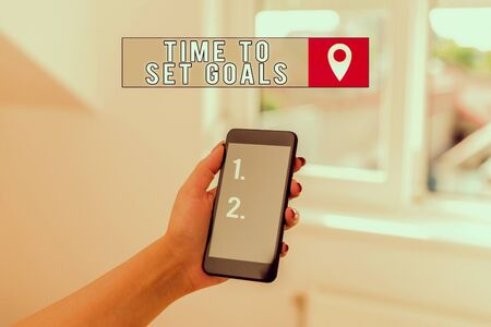 Photo pour Text sign showing Time To Set Goals. Business photo showcasing Desired Objective Wanted to accomplish in the future woman using smartphone office supplies technological devices inside home - image libre de droit