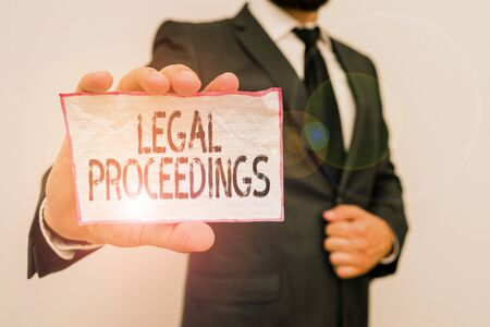 Word writing text Legal Proceedings. Business photo showcasing procedure instituted in a court of law to acquire benefit Male human wear formal work suit office look hold notepaper sheet use hand