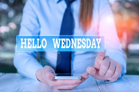 Photo for Handwriting text Hello Wednesday. Conceptual photo Hump day Middle of the working week of the calendar Female business person sitting by table and holding mobile phone - Royalty Free Image