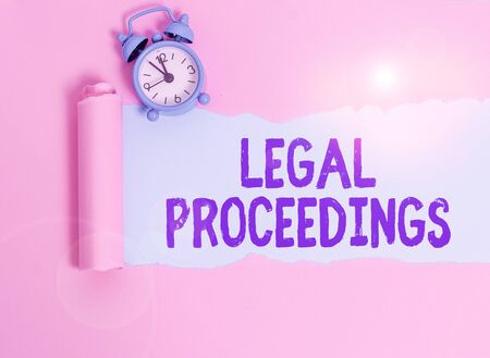 Writing note showing Legal Proceedings. Business concept for procedure instituted in a court of law to acquire benefit Alarm clock and torn cardboard placed above plain pastel table backdrop