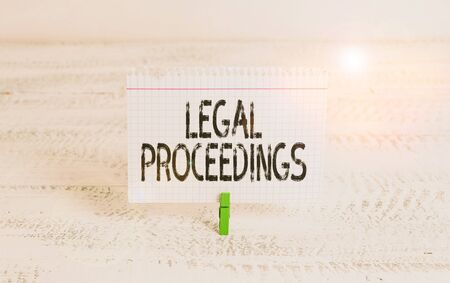 Writing note showing Legal Proceedings. Business concept for procedure instituted in a court of law to acquire benefit Green clothespin white wood background reminder office supply