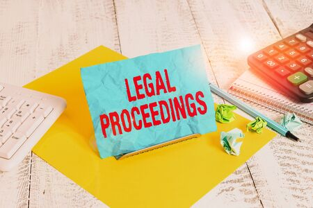 Text sign showing Legal Proceedings. Business photo text procedure instituted in a court of law to acquire benefit Notepaper stand on buffer wire in between computer keyboard and math sheets