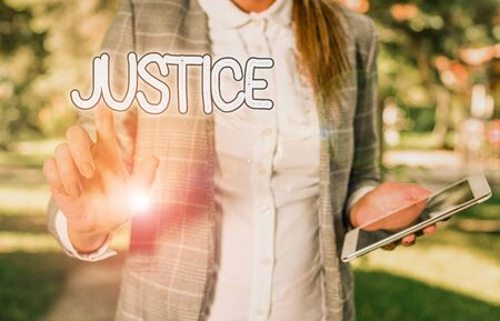 Conceptual hand writing showing Justice. Concept meaning Quality of being just impartial or fair Administration of law rules Business woman sitting with mobile phone and cup of coffee