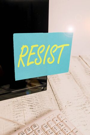 Handwriting text writing Resist. Conceptual photo To fight against something or someone that is attacking you Notation paper taped to black computer monitor screen near white keyboard