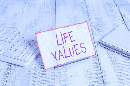 Conceptual hand writing showing Life Values. Concept meaning things that you believe are important in the way you live Notepaper on wire in between computer keyboard and sheets