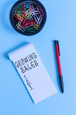 Photo pour Conceptual hand writing showing Growing Sales. Concept meaning Average sales volume of a company products has grown Notebook and stationary with mouse above pastel backdrop - image libre de droit
