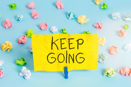 Photo pour Handwriting text writing Keep Going. Conceptual photo make an effort to live normally when in a difficult situation Colored crumpled papers empty reminder blue floor background clothespin - image libre de droit