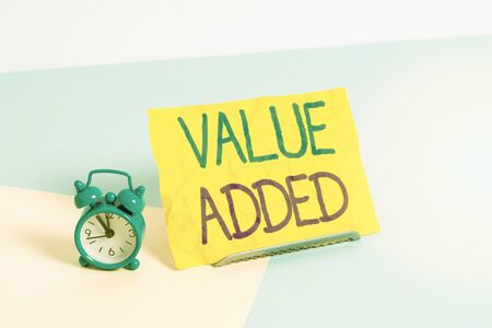 Photo for Handwriting text Value Added. Conceptual photo the extra value created over and above the original value Mini size alarm clock beside a Paper sheet placed tilted on pastel backdrop - Royalty Free Image