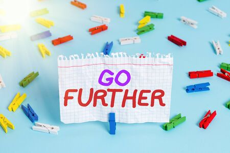 Conceptual hand writing showing Go Further. Concept meaning To make a bolder statement about something being discussed Colored clothespin paper empty reminder blue floor officepin