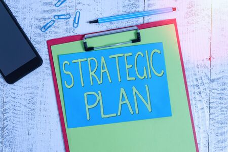 Photo pour Writing note showing Strategic Plan. Business concept for a systematic process of envisioning a desired future Clipboard paper sheet marker note clips smartphone wooden background - image libre de droit