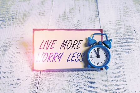 Writing note showing Live More Worry Less. Business concept for Have a good attitude motivation be careless enjoy life Alarm clock tilted above buffer wire in front of notepaper