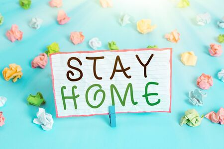 Conceptual hand writing showing Stay Home. Concept meaning not go out for an activity and stay inside the house or home Colored crumpled papers empty reminder blue floor clothespin