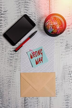 Word writing text Wrong Way. Business photo showcasing taking an unsuitable or undesirable manners or direction Smartphone paper sheet clips holder pen envelope note wooden background