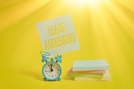 Photo pour Handwriting text writing Lease Agreement. Conceptual photo Contract on the terms to one party agrees rent property Metal alarm clock blank sticky note stacked notepads colored background - image libre de droit