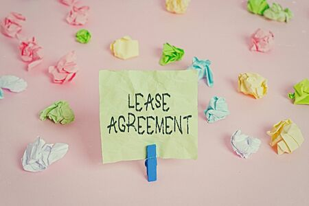 Photo pour Conceptual hand writing showing Lease Agreement. Concept meaning Contract on the terms to one party agrees rent property Colored crumpled papers empty reminder pink floor clothespin - image libre de droit