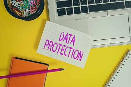 Foto de Text sign showing Data Protection. Business photo showcasing Protect IP addresses and an individualal data from harmful software Laptop pencil sheet clips container spiral notebook colored background - Imagen libre de derechos