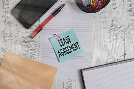 Photo pour Text sign showing Lease Agreement. Business photo showcasing Contract on the terms to one party agrees rent property Smartphone sheet clips ballpoint notebook envelope note wooden background - image libre de droit