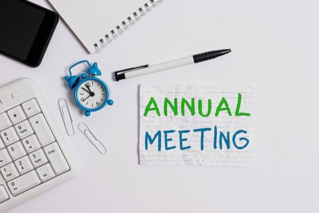 Photo pour Handwriting text writing Annual Meeting. Conceptual photo Yearly gathering of an organization interested shareholders Flat lay above computer mobile phone clock pencil and copy space note paper - image libre de droit
