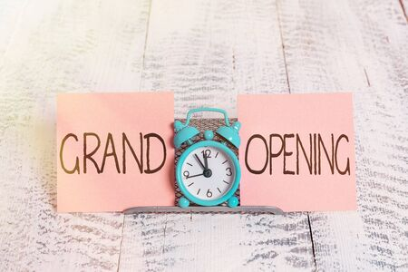 Foto de Writing note showing Grand Opening. Business concept for Ribbon Cutting New Business First Official Day Launching Mini blue alarm clock standing above buffer wire between two paper - Imagen libre de derechos