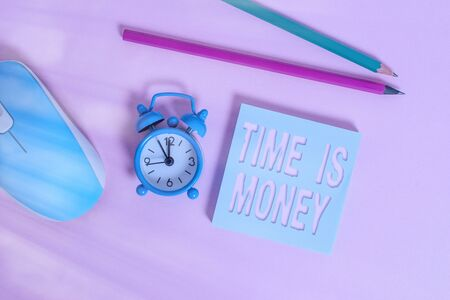 Text sign showing Time Is Money. Business photo showcasing time is a valuable resource Do things as quickly as possible Alarm clock wakeup blank notepad mouse markers colored background