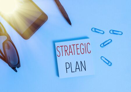 Photo pour Text sign showing Strategic Plan. Business photo text a systematic process of envisioning a desired future Eyeglasses colored sticky note smartphone cell clips pen pastel background - image libre de droit