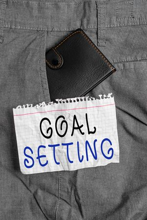 Writing note showing Goal Setting. Business concept for dream big motivational advice or reminder to take action Small wallet inside trouser front pocket near notation paper