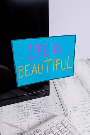 Photo for Word writing text Life Is Beautiful. Business photo showcasing Go to adventure vacation, enjoy and relax to satisfy nature every moment Notation paper taped to black computer monitor screen near white keyboard - Royalty Free Image