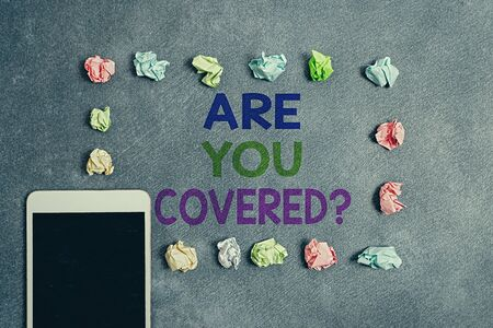 Foto de Writing note showing Are You Covered Question. Business concept for asking if they had insurance in work or life Paper accessories with smartphone arranged on different background - Imagen libre de derechos
