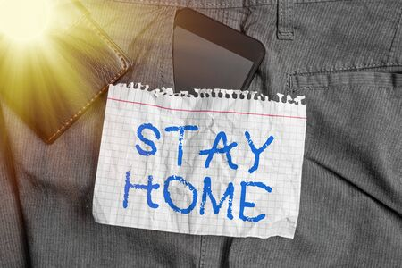 Word writing text Stay Home. Business photo showcasing not go out for an activity and stay inside the house or home Smartphone device inside trousers front pocket with wallet and note paper