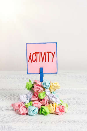 Text sign showing Activity. Business photo text the condition where many things are happening or move around Reminder pile colored crumpled paper clothespin reminder white wooden space