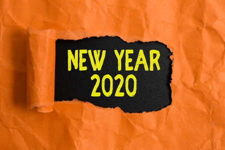 Text sign showing New Year 2020. Business photo text Greeting Celebrating Holiday Fresh Start Best wishes Rolled ripped torn cardboard placed above a wooden classic table backdrop