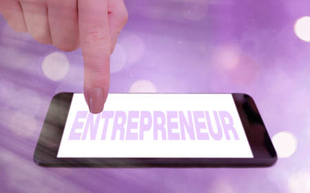 Conceptual hand writing showing Entrepreneur. Concept meaning one who organizes and assumes the risks of a business Modern gadgets white screen under colorful bokeh background