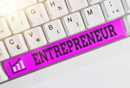 Conceptual hand writing showing Entrepreneur. Concept meaning one who organizes and assumes the risks of a business Colored keyboard key with accessories arranged on empty copy space