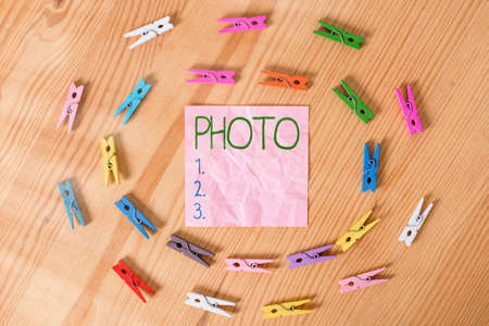 Conceptual hand writing showing photo. Concept meaning defined as produced by light, image taken with the help of light. Colored crumpled papers wooden floor background clothespin