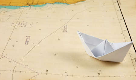 Paper boat on a navigational chart.
