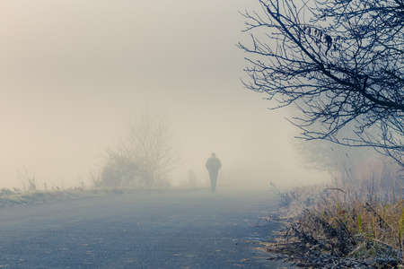 A person walk into the misty foggy road in a dramatic sunrise scene with abstract colors