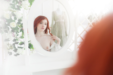 Foto de Tender portrait of a young dreamy redhead woman wearing beautiful vintage dress. She is sitting in front of the mirror with naked breast - Imagen libre de derechos