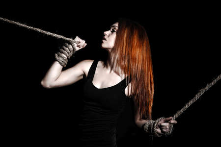 Beautiful young woman with bright red hair and tied arms over black background