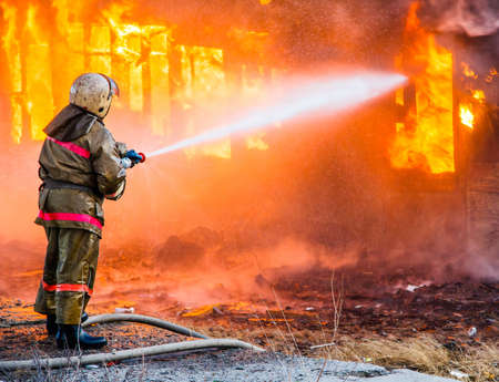 Photo for Fireman extinguishes a burning old wooden residential house. - Royalty Free Image