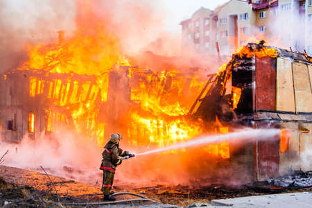 Foto de Fireman extinguishes a fire in an old wooden house - Imagen libre de derechos
